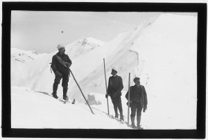 narciarze stojący w strojach z początku XX wieku