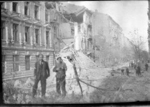 dwóch mężczyzn stojących na tle zburzonej Warszawy