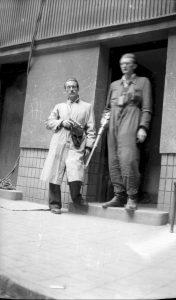 dwóch powstańców warszawskich, stoją przed wejściem do jednej z kamienic