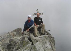 dwie osoby siedzące przy krzyżu na Gerlachu