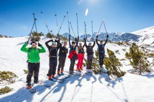 narciarze na nartach na śniegu z podniesionymi kijkami