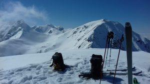 plecaki narty i kijki narciarzy na tle gór