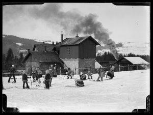 Czarnobiałe zdjęcie. Grupa osiemnastu osób, w tym trzy osoby dorosłe i piętnaścioro dzieci. Dzieci zapinają narty. Na drugim planie zabudowania dworca kolejowego i dym z lokomotywy. Tłem są zbocza Pasma Gubałowskiego.