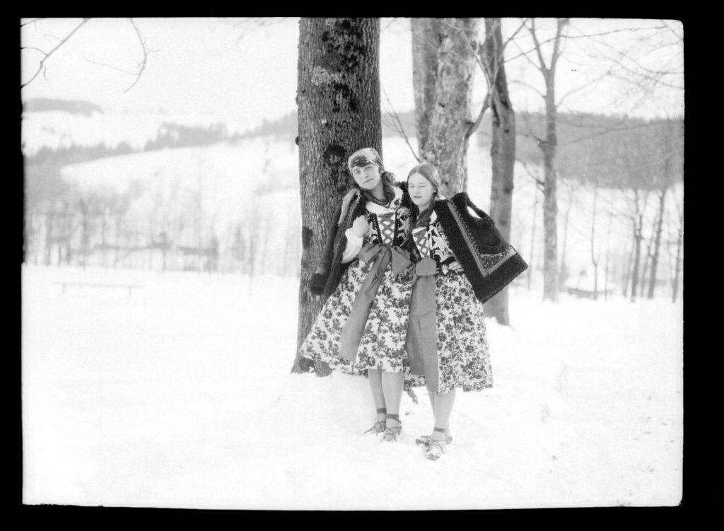 Dwie dziewczyny w zimowej scenerii ubrane w stroje góralskie, zdjęcie z początku wieku 20-tego