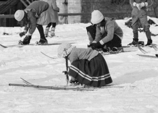 Czarnobiałe zdjęcie – fragment zdjęcia głównego. Dziewczynka w spódniczce, schylona, zapina narty.