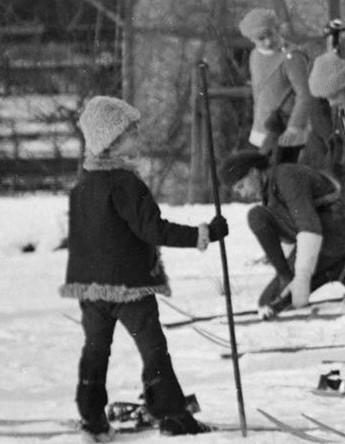 Czarnobiałe zdjęcie – fragment zdjęcia głównego. Chłopiec z jednym, bambusowym kijem narciarskim.