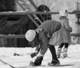 Czarnobiałe zdjęcie – fragment zdjęcia głównego. Dziewczynka w spódniczce zapina narty, widoczny jest typ zapięcia narciarskiego.
