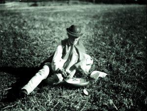 """Zdjęcie przedstawia górala siedzącego na trawie, który spożywa podwieczorek (w gwarze góralskiej nazywany """"juzyna"""")"""