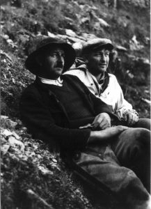 Czarno-białe zdjęcie, dwie osoby opierają się o stromy stok