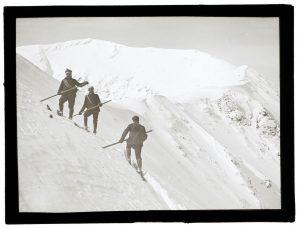 Czarno-białe zdjęcie, trzech narciarzy na zaśnieżonym stoku