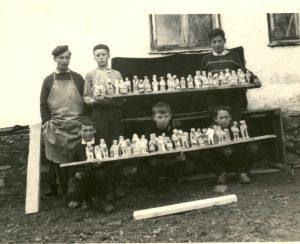 stare zdjęcie przedstawia dwie półki z rzeźbami, za którymi widać 5 dzieci i obok rzeźbiarza