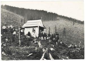 kapliczka na wykarczowanym stoku, wokół niej zgromadzeni ludzie w strojach góralskich
