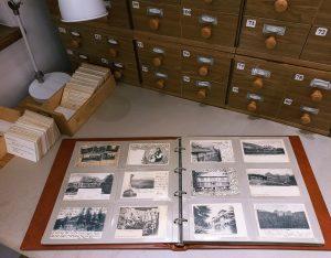 otwarty album ze starymi fotografiami, w tle lampka i biblioteczna kartoteka